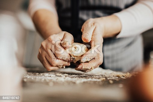 istock Close-up of woman's hands kneading dough 649219742