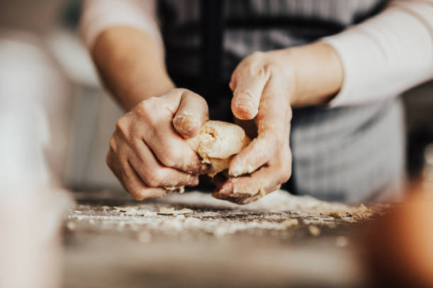 Close-up of woman's hands kneading dough stock photo
