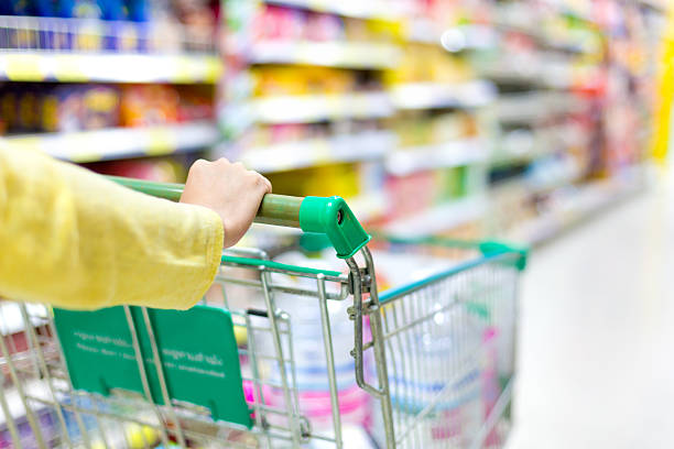 Closeup of  woman's hands pushing a shopping cart stock photo