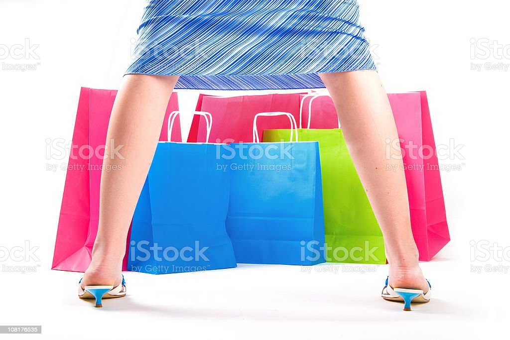 Close-Up of Woman's Legs Facing Shopping Bags stock photo
