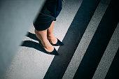 Close-up of woman's legs in high heels on sidewalk