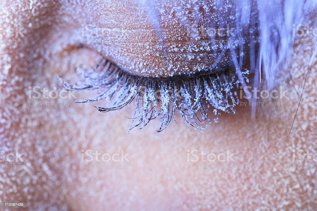 Close-up of woman's tinted closed eye with frost frozen on stock photo