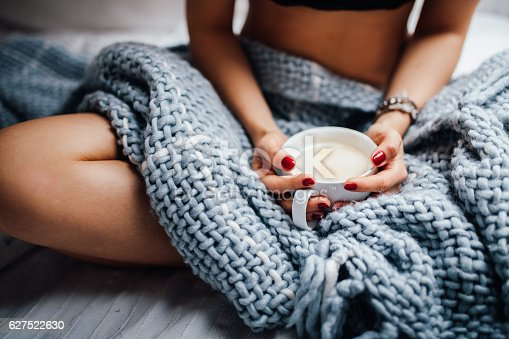 istock Close-up of women holding fresh cup of coffee in bed 627522630