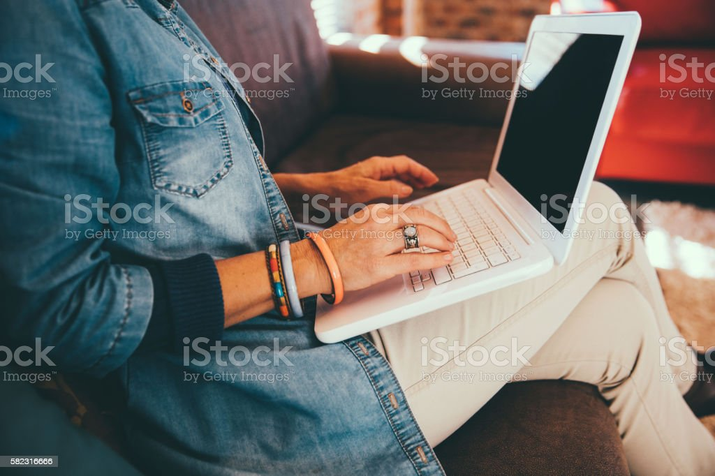 Close-up of women typing on keyboard on her laptop at stock photo