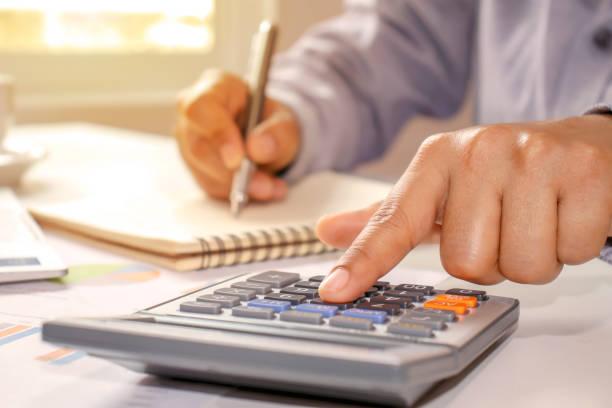 primer plano de las mujeres usando calculadoras y toma de notas, informes contables, ideas de cálculo de costos y ahorro de dinero. - gerente de cuentas fotografías e imágenes de stock