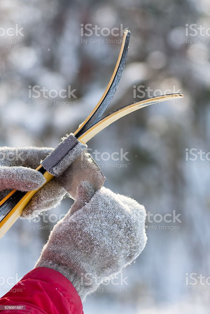 closeup of women's hands wrapping velcro ski strap stock photo