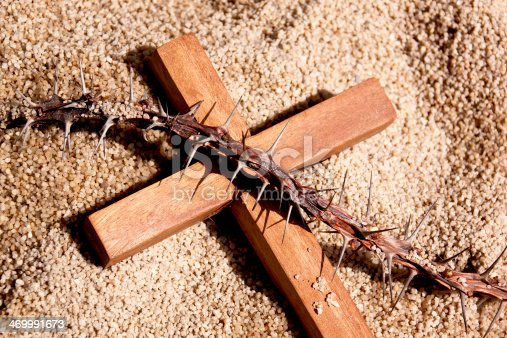 istock Closeup of Wooden Cross and Thorns on Sand Background 469991673