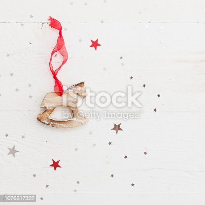 istock Closeup of wooden horse Christmas decoration on vintage wooden background with shiny stars. New Year, holidays and celebration concept 1076617322