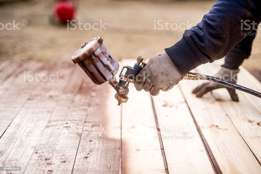 close-up of worker hand using spray gun and painting wood stock photo