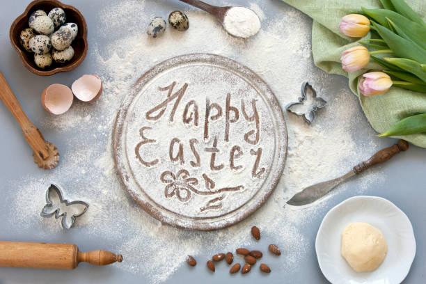 Close-up do local de trabalho com farinha e codorna ovos em uma tigela de cerâmica marrom mesa cinza com flores tulipa. Feliz Páscoa. Vista superior, plano de fundo - foto de acervo
