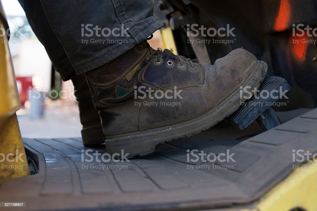 Close-up of worn construction work boots on forklift stock photo