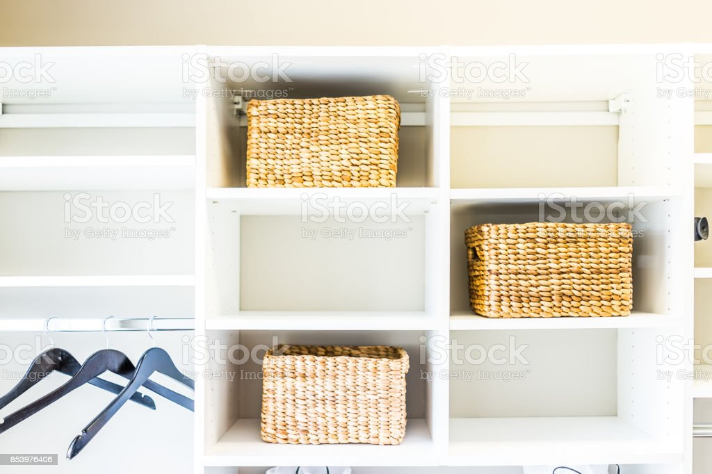 Closeup of woven straw baskets in modern minimalist white closet or laundry room with bright light in staging model house or apartment with hangers stock photo