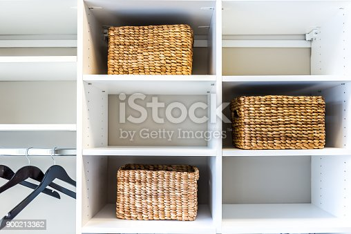 istock Closeup of woven straw baskets in modern minimalist white closet or laundry room with bright light in staging model house or apartment with hangers 900213362