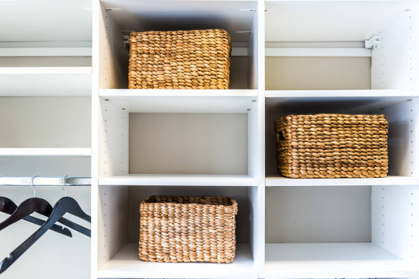 Closeup of woven straw baskets in modern minimalist white closet or laundry room with bright light in staging model house or apartment with hangers Closeup of woven straw baskets in modern minimalist white closet or laundry room with bright light in staging model house or apartment with hangers neat stock pictures, royalty-free photos & images