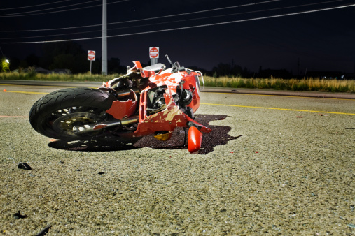 Crash scene.  Red motorcycle laying on its side on the street.  Illuminated by a overhead street light.