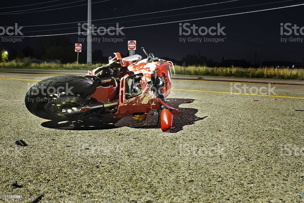 Close-up of wrecked red motorcycle on side of road stock photo