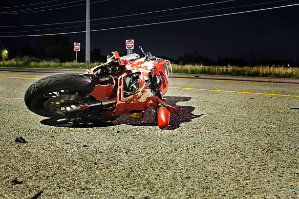 Close-up of wrecked red motorcycle on side of road Crash scene.  Red motorcycle laying on its side on the street.  Illuminated by a overhead street light. misfortune stock pictures, royalty-free photos & images
