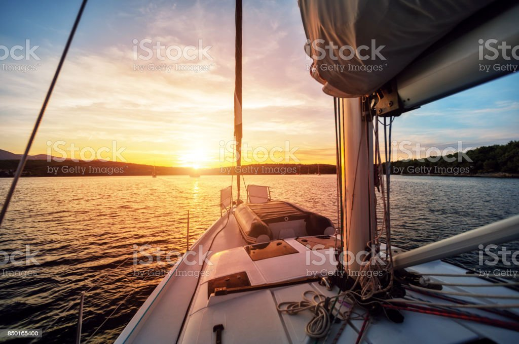 Close-up of yacht sailing against beautiful sunset stock photo