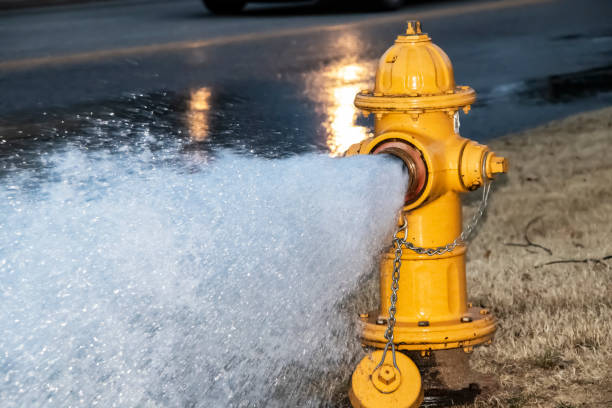 Close-up of yellow fire hydrant gushing water across a street with wet highway and tire from passing car behind Close-up of yellow fire hydrant gushing water across a street with wet highway and tire from passing car behind flushing water stock pictures, royalty-free photos & images