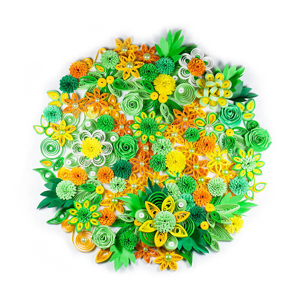 Closeup of yellow, green, orange and white paper quilling flowers stock photo