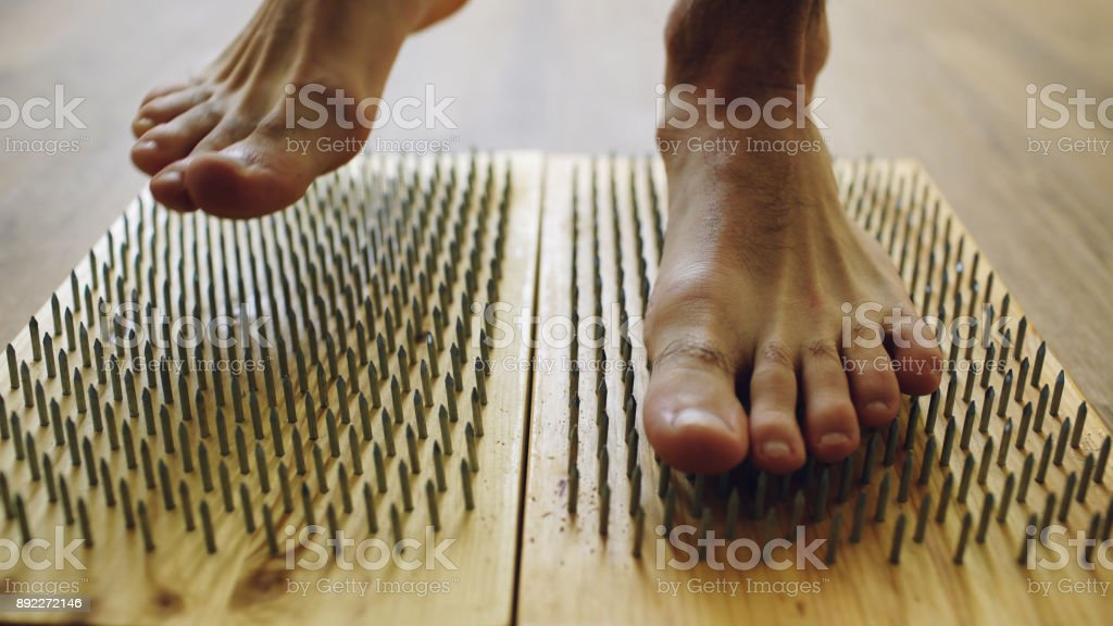 Closeup of yoga man stand on board with sharp nails stock photo