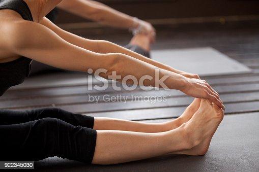 istock Closeup of yogi woman in paschimottanasana pose 922345030