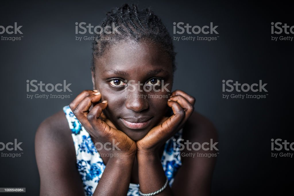 Close-up of young afro woman with hands on chin stock photo