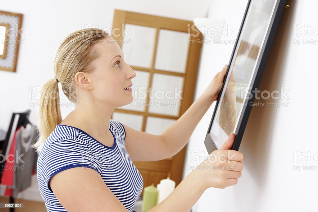 close-up of young attractive woman hanging picture on a wall stock photo