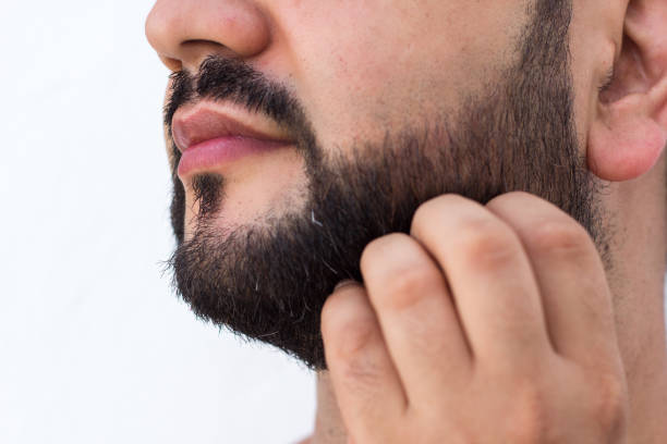 Close-up of young bearded man touching his beard , scratching beard, thoughtful gesture stock photo
