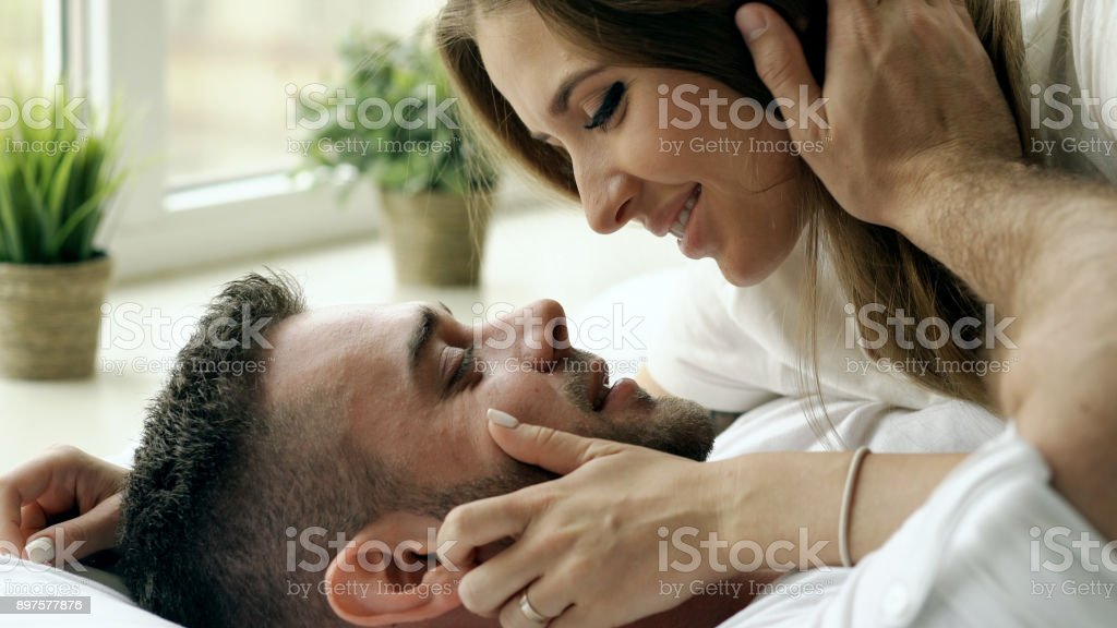 Closeup of Young beautiful and loving couple play and kiss in bed at the morning. Attractive man kissing and hugging his wife in bed stock photo