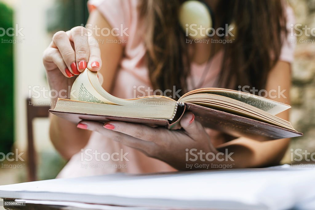 Closeup of young beautiful female sitting outside and studying hard. stock photo