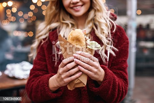 Woman with sandwich outdoors. Close-up of young blonde woman in red cap and eco fur coat is eating out sandwich at sandwich bar at street fair.
