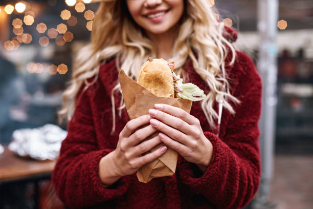 Close-up of young blonde woman eating out sandwich at sandwich bar Woman with sandwich outdoors. Close-up of young blonde woman in red cap and eco fur coat is eating out sandwich at sandwich bar at street fair. female sandwich stock pictures, royalty-free photos & images