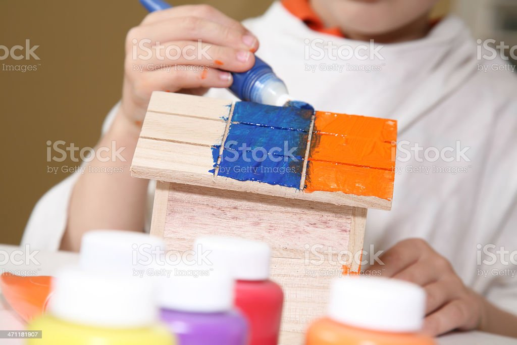 Closeup of Young Boy Painting a Bird House royalty-free stock photo