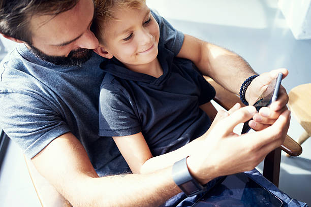 Closeup of young boy sitting with father and using mobile – Foto