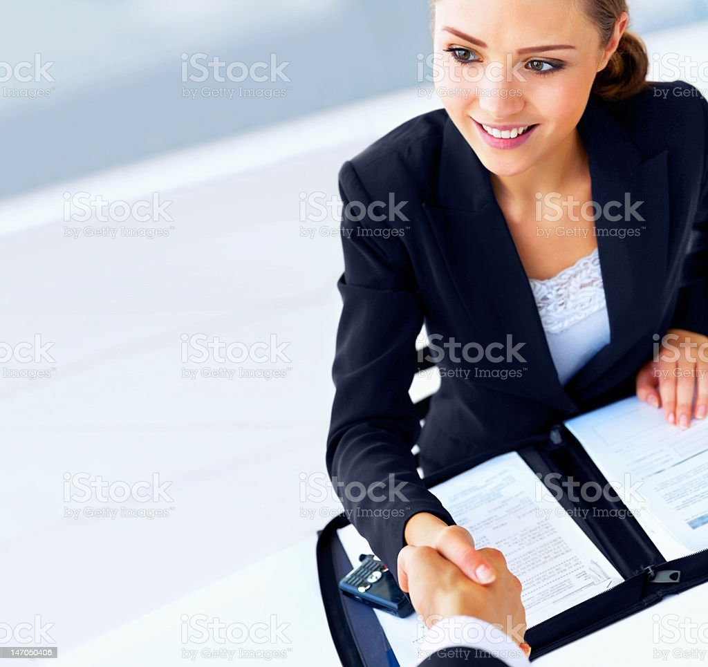 Close-up of young businesswoman shaking hand with colleague royalty-free stock photo
