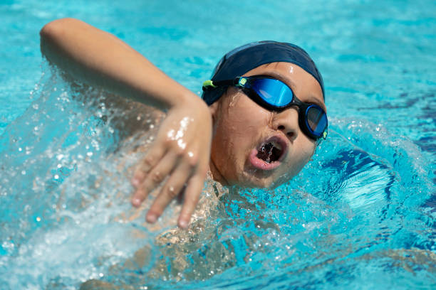 Close-up of young chinese boy swimming freestyle stock photo