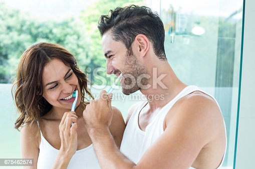 675462768istockphoto Close-up of young couple brushing teeth 675462574
