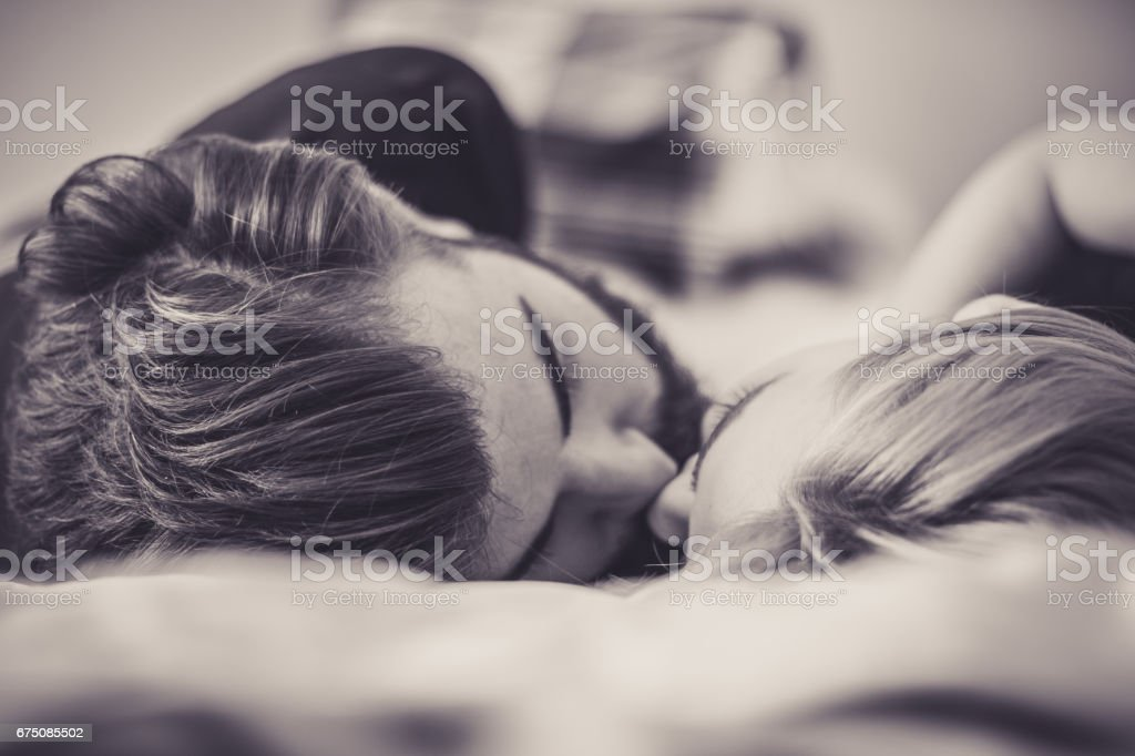 Close-up of young couple kissing in the bed stock photo