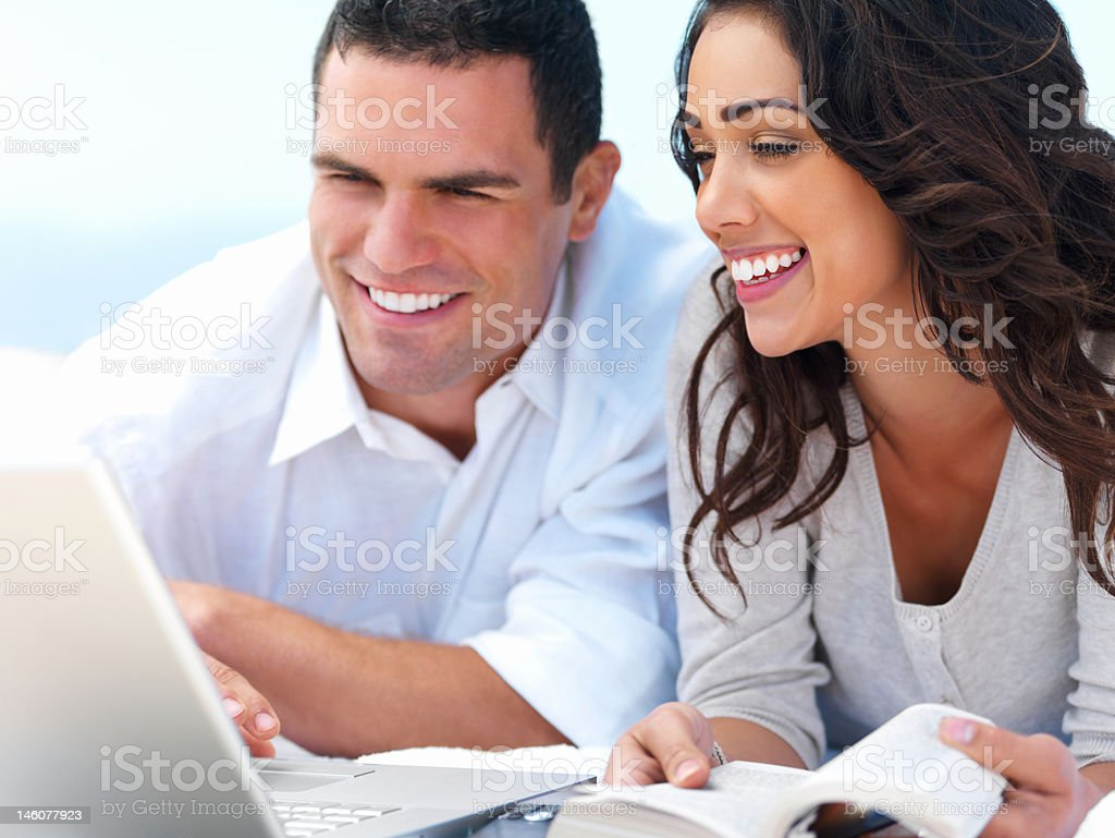 Close-up of young couple looking at laptop and smiling royalty-free stock photo