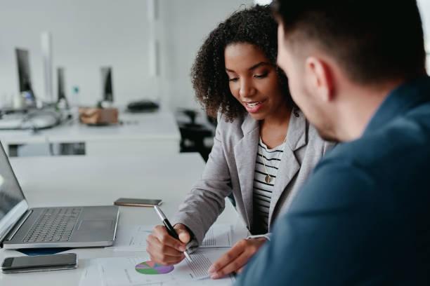 primer plano de la joven ejecutiva discutiendo el plan de negocios a su colega con gráfico y gráfico en el escritorio - financial planning fotografías e imágenes de stock