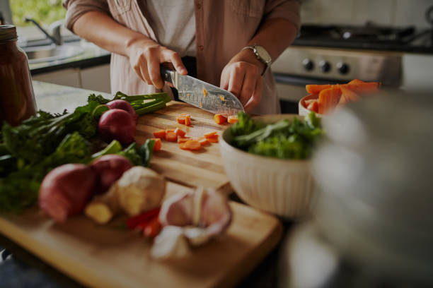 primo piano di giovani mani femminili che tagliano verdure fresche sul tagliere mentre si trova nella cucina moderna - preparando un pasto sano per aumentare il sistema immunitario e combattere il coronavirus - cucinare foto e immagini stock