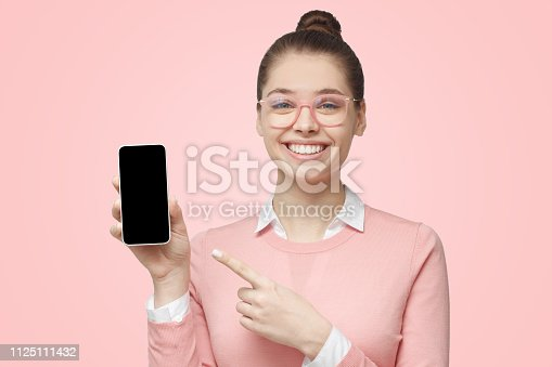 istock Close-up of young female holding blank cellphone screen and showing it with smile, copy space for application included, isolated on pink background 1125111432