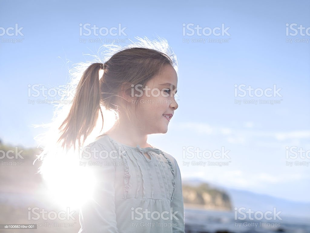 Close-up of young girl (6-7) at beach, backlit royalty-free stock photo