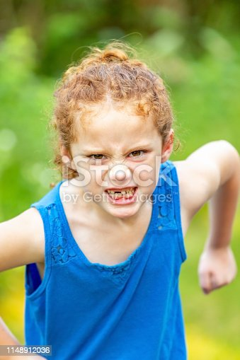 Close-up of a young girl pretending to be mad. Her curly red hair is pulled back in a ponytail, and she is wearing a blue tank top on this summer day. She is missing a top front tooth.