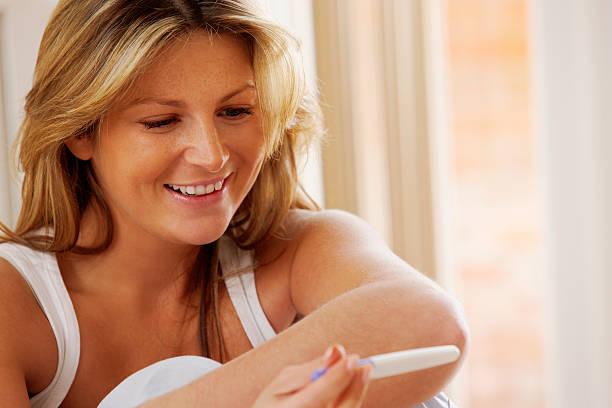 nahaufnahme des jungen glückliche frau, die schwangerschaftstest zu hause fühlen - versuche nicht zu lachen stock-fotos und bilder