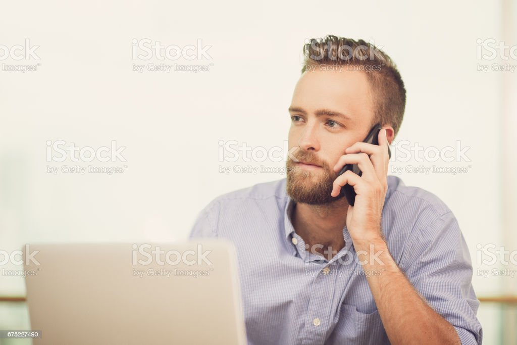 Closeup of Young Man Calling on Phone with Laptop royalty-free stock photo