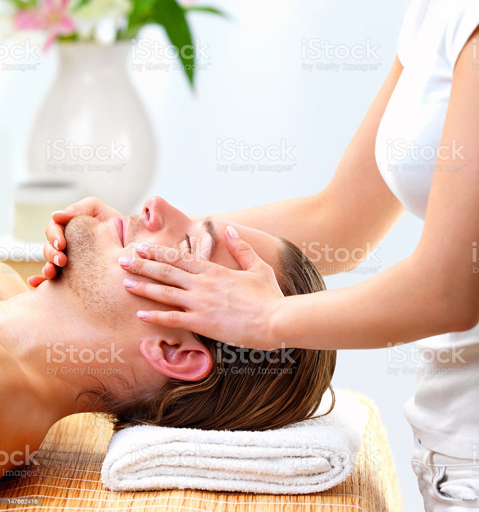 Close-up of  young man receiving facial massage at day spa royalty-free stock photo