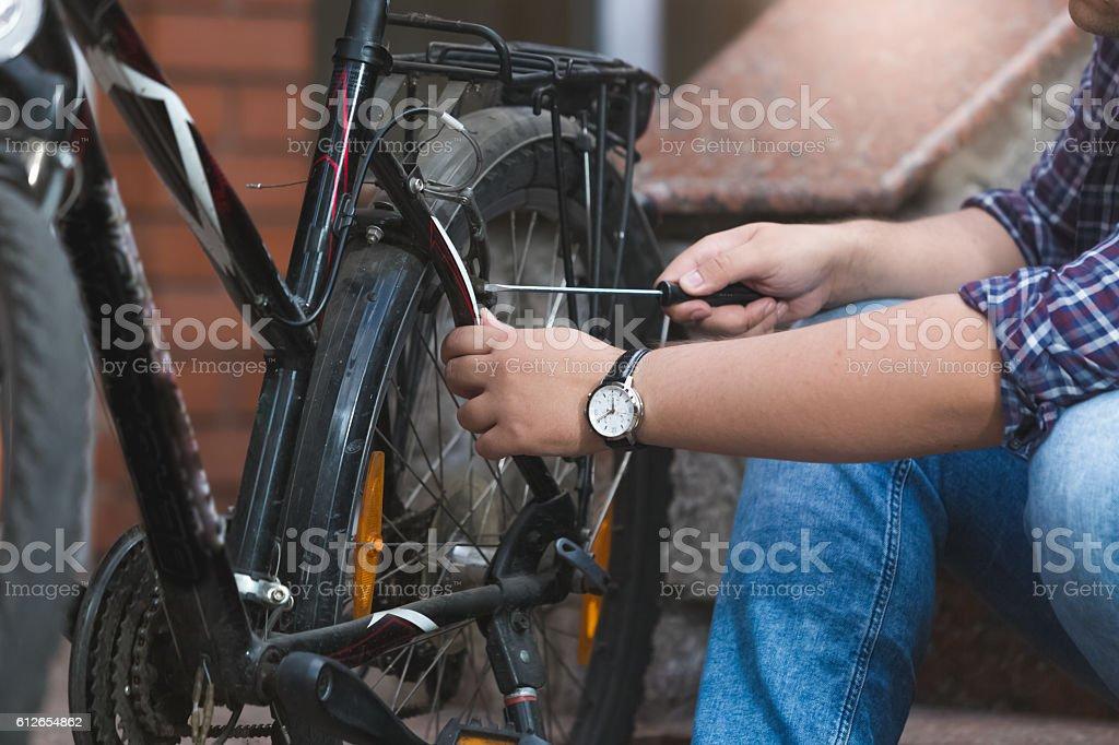 Closeup of young man repairing bicycle rear wheel stock photo