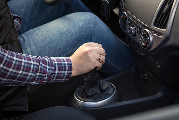 Closeup of young man shifting manual gearbox in car Closeup shot of young man shifting manual gearbox in car vehicle clutch stock pictures, royalty-free photos & images